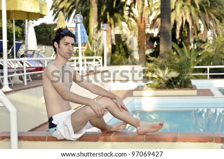 Serious young model at the swimming pool - stock photo