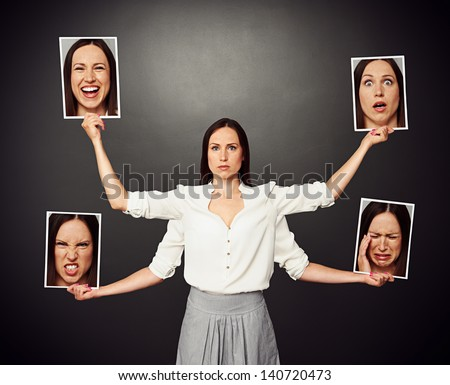 serious young woman holding pictures with different mood - stock photo