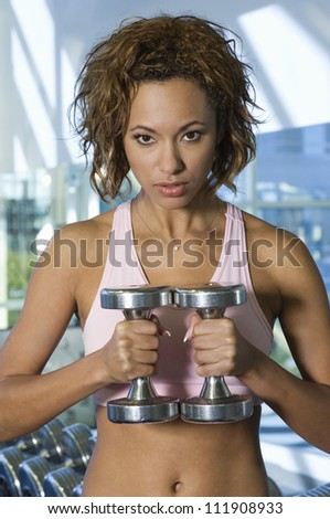 Serious young woman lifting weights at a gym - stock photo