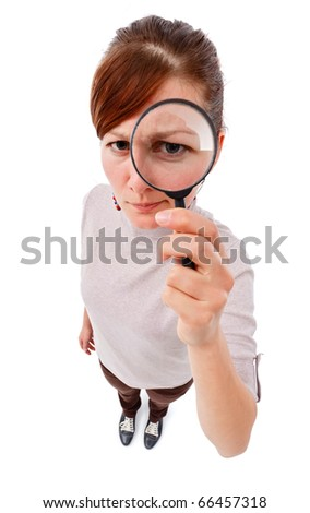 Serious young woman looking through magnifier lens as detective, analyzing or finding something - stock photo
