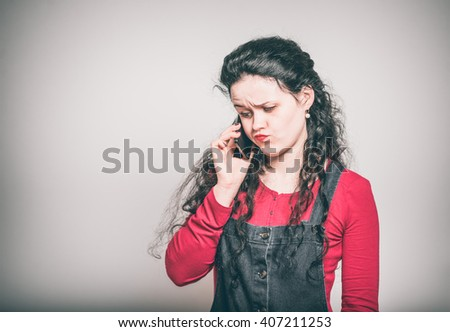 serious young woman talking on the phone, wearing a overalls, close-up isolated on a gray background - stock photo
