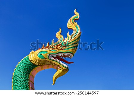serpent king or king of naga statue in thai temple on blue sky background    - stock photo