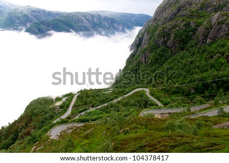 Serpentine road leading to the top of the mountain Kjerag - stock photo