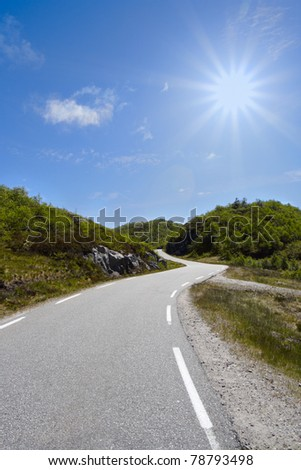 serpentine road running through the hills of trees - stock photo