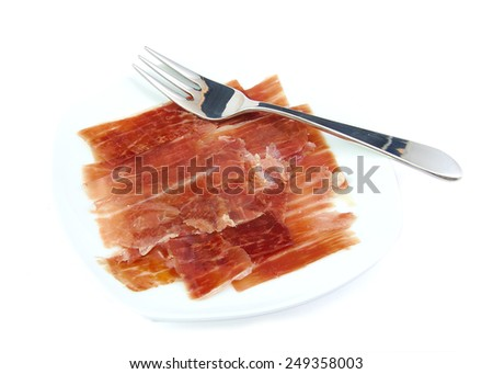 Serrano ham on a white dish with a metal fork. Jabugo. Spanish tapa - stock photo