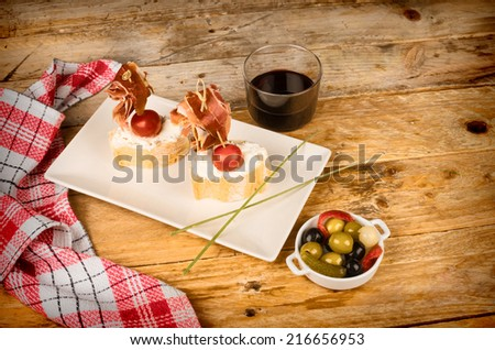 Serrano ham tapa served on bread with goat cheese - stock photo