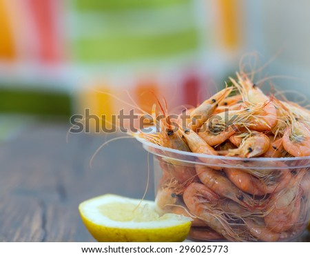 Serve cooked shrimp and lemon on a bar table. Delicious fresh cooked shrimp prepared to eat. Cooked shrimps with lemon on wooden table. Snack to beer and wine. Shrimp from the Black Sea. - stock photo