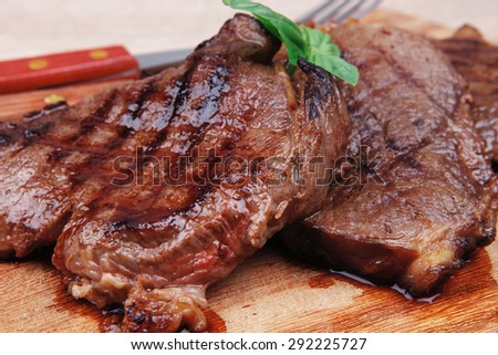 served beef meat barbecue on wooden plate with cutlery - stock photo