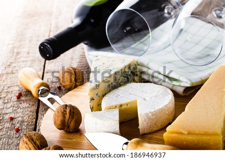 served cheese and wine on old wooden table - stock photo