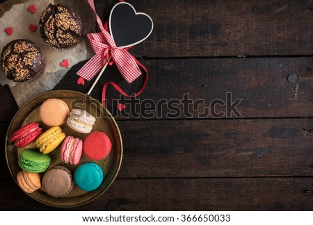 Served chocolate muffins and colorful macaroons cookies on wooden background,valentine day concept and blank space  - stock photo