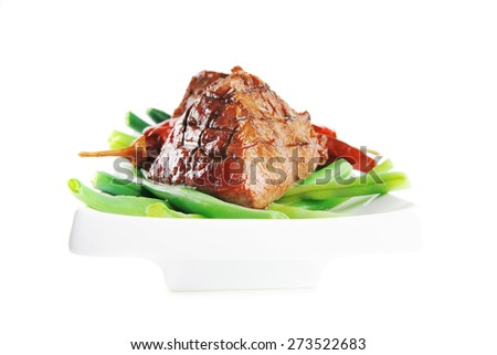served grilled beef veal fillet entrecote on a white plate with peppers and green peas on long plate isolated on white background - stock photo