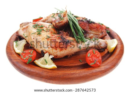 served grilled chicken legs with tomatoes lemon and chives on wooden plate isolated on white background - stock photo