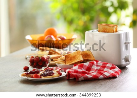 Served table for breakfast with toast and fruit, on blurred background - stock photo