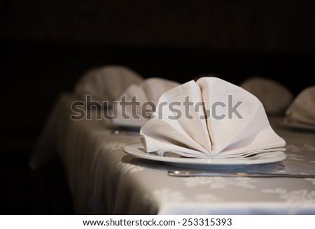 Served table with napkins in dark restoran - stock photo