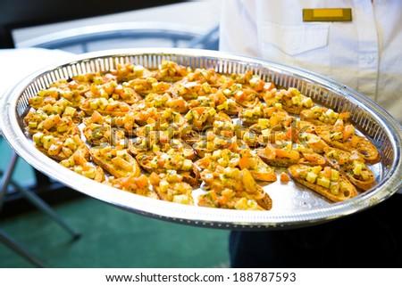 Server holding an appetizer platter at a wedding reception. - stock photo