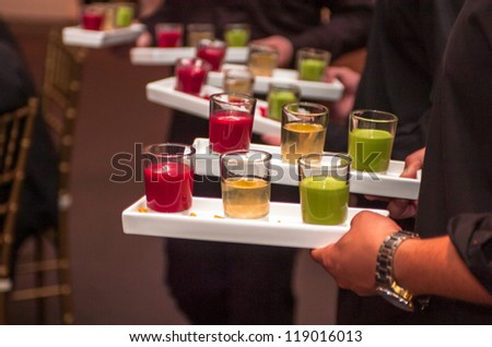 Servers holding trays of multicolored shot glasses - stock photo