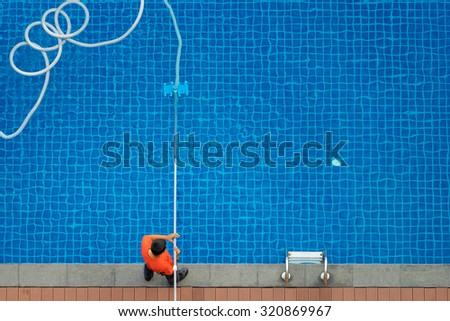Service and technology. Top view of man cleaning swimming pool with vacuum robot. - stock photo