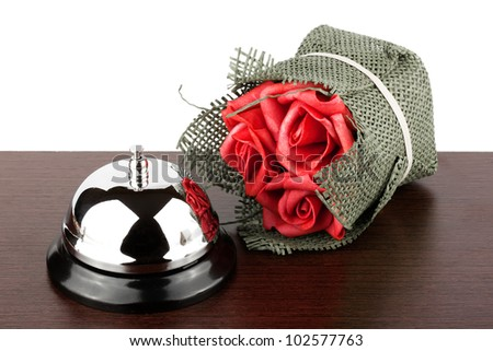 Service Bell and red roses at wooden Hotel Desk - stock photo