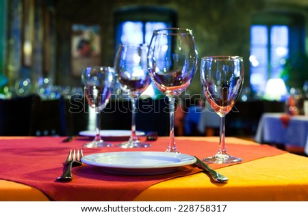 Service for two persons: table in a restaurant with a red and orange tablecloth, wine glasses, white plates and cutlery. (Soft focus.) - stock photo