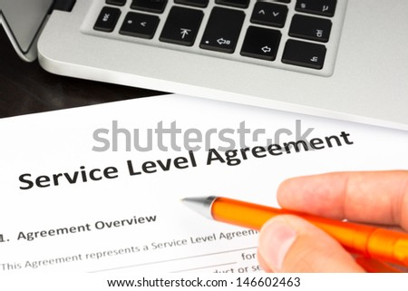 Service Level Agreement Contract Form with Hand and Pen - stock photo