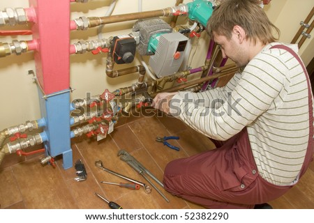 Service man at work. Servicing water & heating systems - stock photo