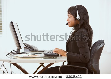 Service: Side View Of Woman At Modern Desk Set Up - stock photo