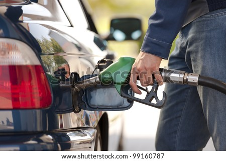 Service station worker filling up car with fuel, close-up - stock photo