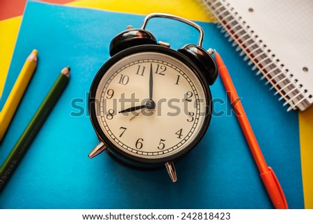 service time watch clock dial pencil pen colored paper address book notebook colored pencils blue red yellow white spiral morning lesson lecture break waiting - stock photo