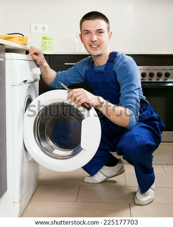 Service worker repairing washing machine - stock photo