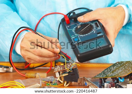 Serviceman checks electronic hardware with a multimeter in the service workshop - stock photo