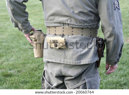 Serviceman in army uniform with canteen and gun. - stock photo