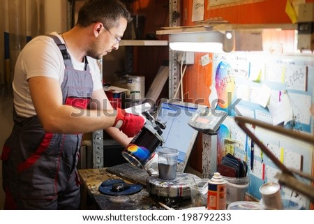 Serviceman mixing paint in a car body workshop - stock photo