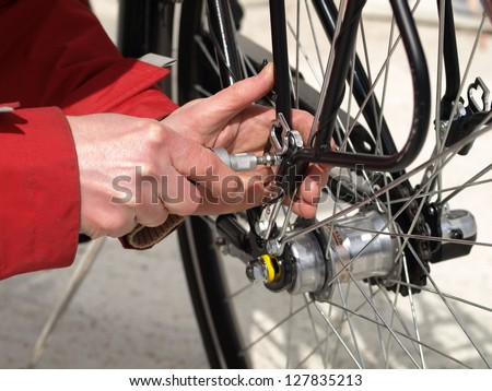 Serviceman repairing a bicycle tire with tools - stock photo