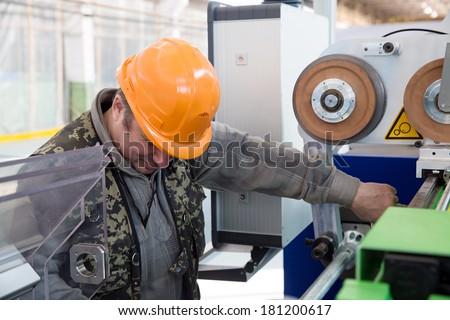 Serviceman worker engineer during maintenance modern industrial machine in factory workshop - stock photo