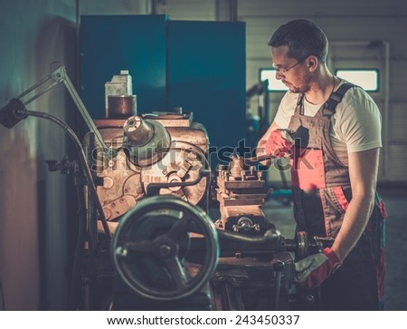 Serviceman working on lathe machine in car workshop - stock photo