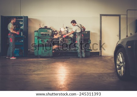 Serviceman working on turning lathe in car workshop - stock photo