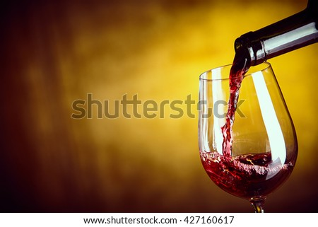 Serving a glass of red wine from a bottle with a close up view of the wine being poured into the bowl of an elegant wine glass over an abstract yellow brown background with copy space - stock photo