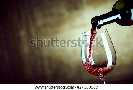 Serving a single glass of red wine from a bottle with a close up view of the neck of the bottle and glass over a wide angle abstract brown background with copy space - stock photo