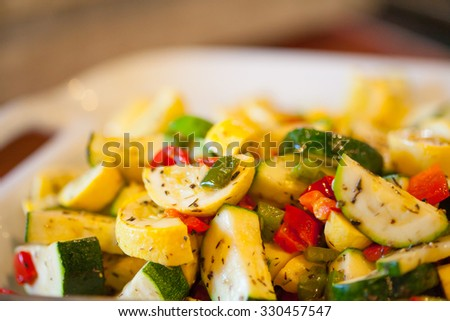 Serving bowl with herbed zucchini and yellow squash with sweet peppers - stock photo