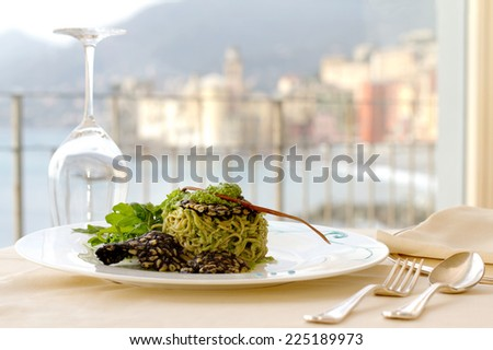 serving dish with home made pasta with rocket pesto and pine nuts crusted squid ink against Camogli background - stock photo