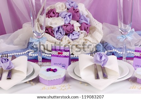 Serving fabulous wedding table in purple color on white and purple fabric background - stock photo