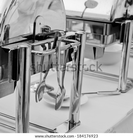 Serving kitchen tongs with chafing dish - stock photo