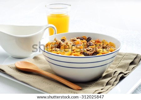 Serving of a nutritious bowl of cereal and orange juice  - stock photo