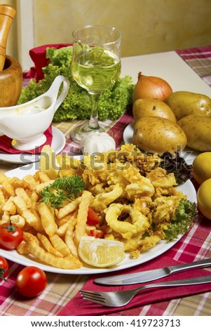 Serving of breaded and deep-fried calamari and fries on a white plate served on a table with fresh vegetables,  dressing sauce, lemon and a glass of white wine. - stock photo