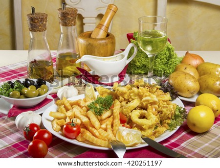 Serving of breaded and deep-fried calamari and fries on a white plate served on a table with fresh vegetables, olives, dressing sauce, edible oil, lemon and a glass of white wine. - stock photo