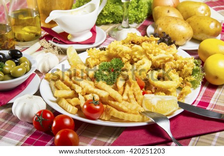 Serving of breaded and deep-fried calamari and fries on a white plate served on a table with fresh vegetables, olives, dressing sauce, edible oil and lemon. - stock photo