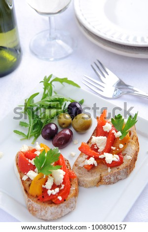 Serving of canapes; bread with roasted peppers and feta cheese and mixed olives served with wine - stock photo