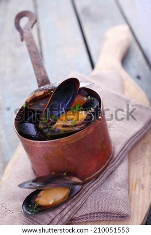 Serving of delicious gourmet freshly steamed marine mussels in a copper pot with an open one displayed below on a napkin in a rustic kitchen - stock photo