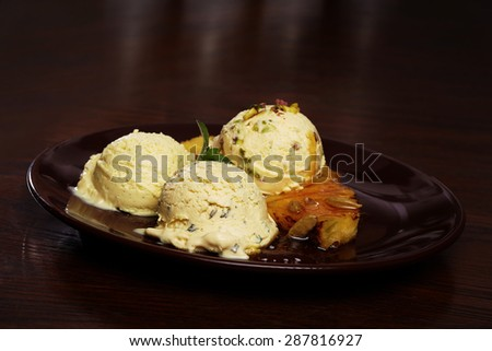 Serving of delicious home made vanilla ice cream with pistachio nuts, grilled pineapple and caramel topping - stock photo