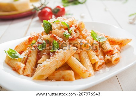 Serving of spicy savory italian penne pasta garnished with fresh basil and topped with grated Parmigiano-Reggiano, or parmesan, cheese - stock photo